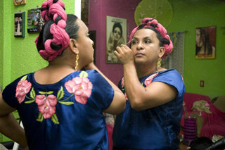 A man plucks his eyebrows dressed in the traditional costume of a Zapotec woman at the town of Juchitan (Reuters)