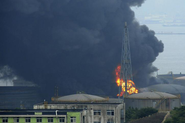 Smoke rises amid storage tanks during a fire at a PetroChina's refinery in Dalian (Reuters)