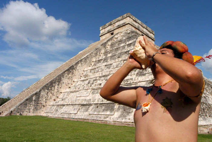 A man plays a shell to invoke the Mayan God 'Kukulcan' in front of the Chichen Itza pyramid in Chichen Itza, Mexico (AAP)