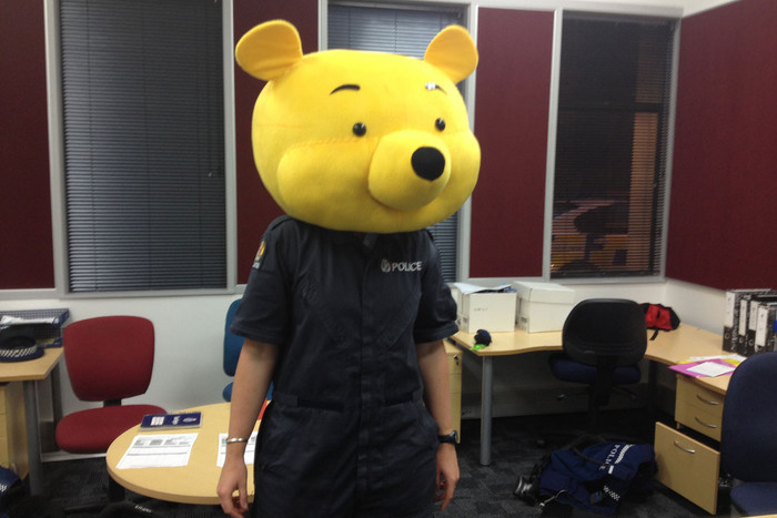 A police officer models the stolen Winnie the Pooh costume
