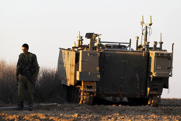 An Israeli soldier walks near an armoured personnel carrier near Gaza strip (Reuters)