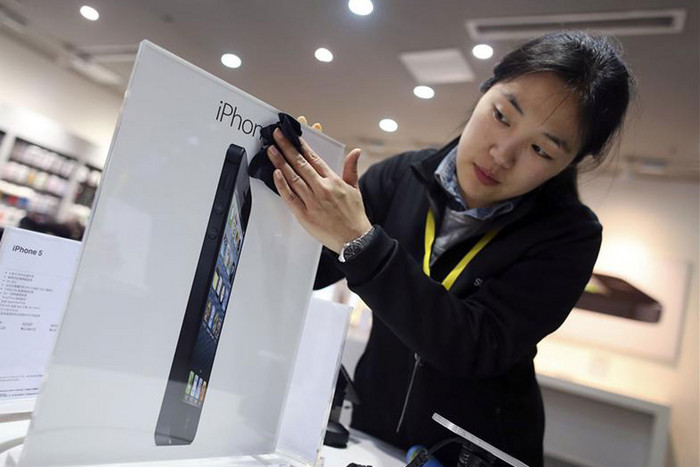 An employee cleans an advertisement plate at an Apple dealership on eve of iPhone 5's release, in Wuhan (Reuters)