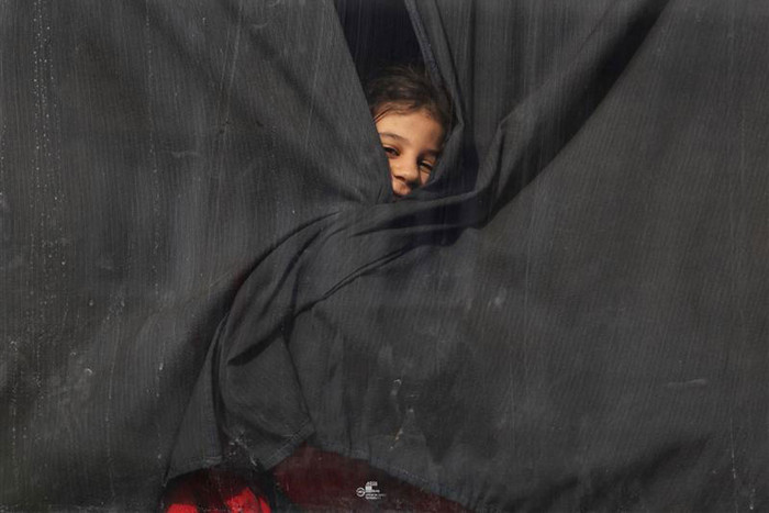 Palestinian girl, who had been living at Yarmouk Palestinian refugee camp in Syria, looks out of a bus window, as the bus arrives at the Lebanese-Syrian border (Reuters)