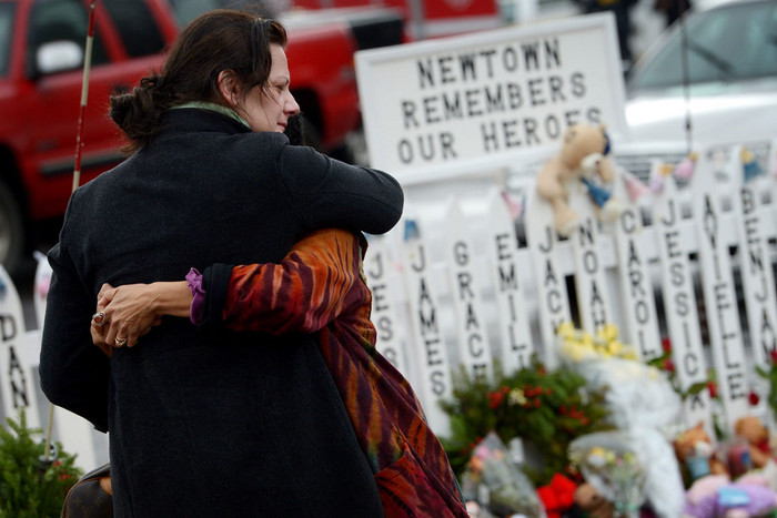 Two women embrace in front of a fence with the names of the 20 children killed a week ago at a memorial at the Sandy Hook Elementary School in Newtown, Connecticut (AAP)