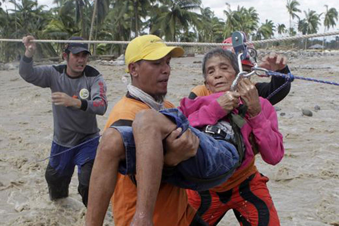 A rescuer evacuates a typhoon victim to higher ground in New Bataan (Reuters)