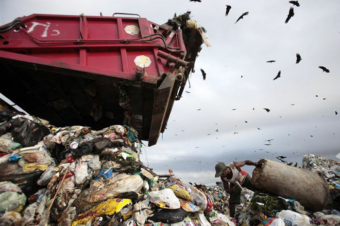A man collects recyclable materials on the last day of the Jardim Gramacho landfill in Rio de Janeiro (Reuters)