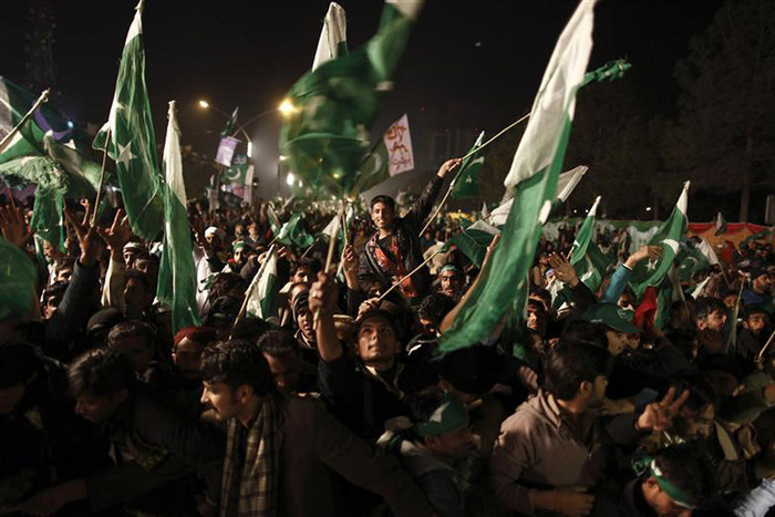 Supporters of Muhammad Tahir-ul-Qadri wave Pakistani flags during a protest in Islamabad (Reuters)