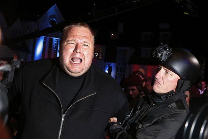 An actor in police costume mock-arrests Kim Dotcom as he launches his new website