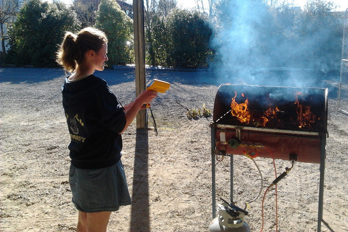 Lincoln University student Jenny Dent measures temperatures of burning gorse on the 'plant BBQ'; temperatures are measured using an infrared thermometer (Photo: Tim Curran)