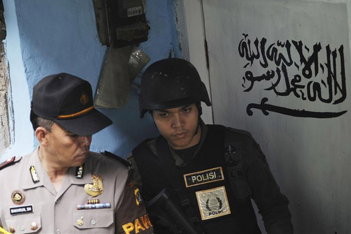 An official from the Special Detachment 88 squad and a police officer stand guard outside the house of a suspected militant in Jakarta (Reuters file)