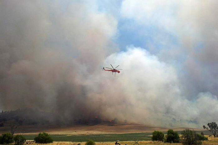 A helicopter flies over a bushfire burning near Oura, NSW (AAP)
