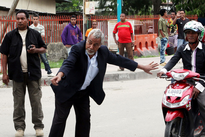 Timor-Leste's Prime Minister Xanana Gusmao (C) directs motorists as he tries to clear a traffic jam outside the presidential office in Dili (EPA/AAP)