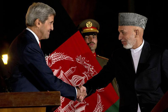 Afghanistan's President Hamid Karzai (R) shakes hands with US Secretary of State John Kerry after a news conference at the Presidential Palace in Kabul October 12 (Reuters)