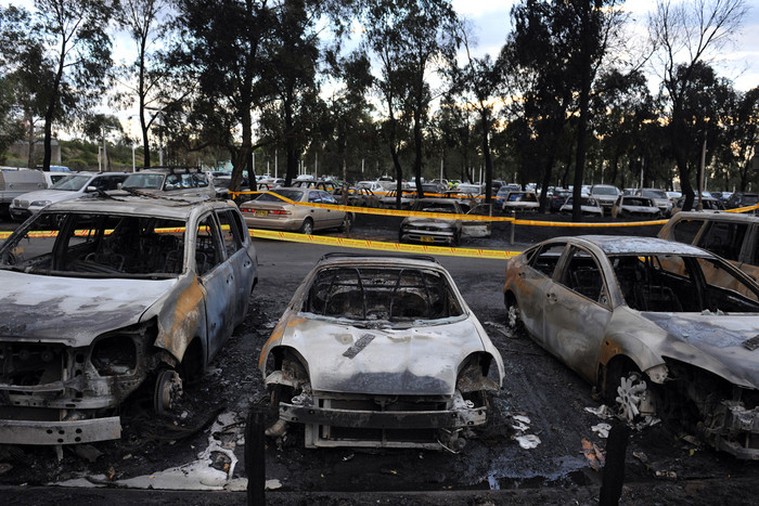 Burnt out vehicles line the carpark next to the Olympic Park Aquatic Centre (AAP)
