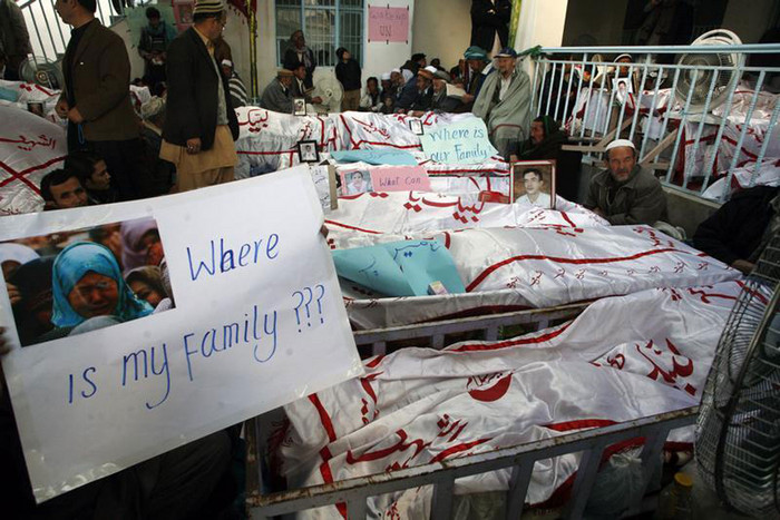 Shi'ite Muslims sit next to covered bodies killed in Saturday's bomb attack during a protest in Quetta (Reuters)