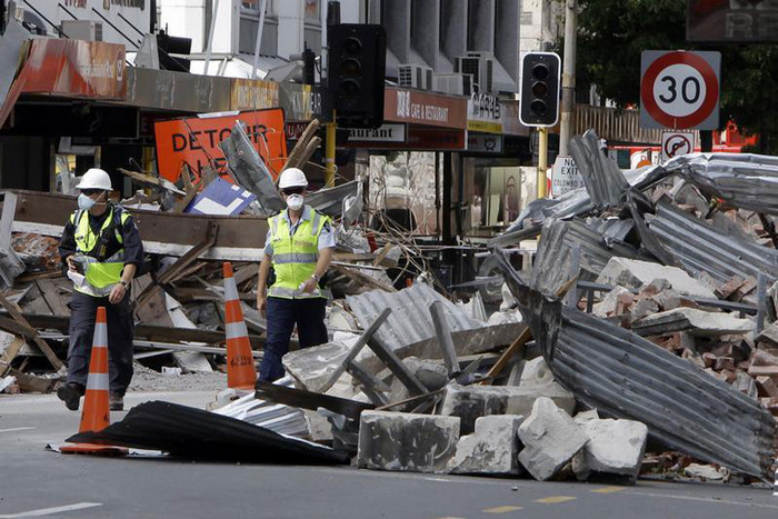 Police officers walk through rubble in central Christchurch (Reuters)