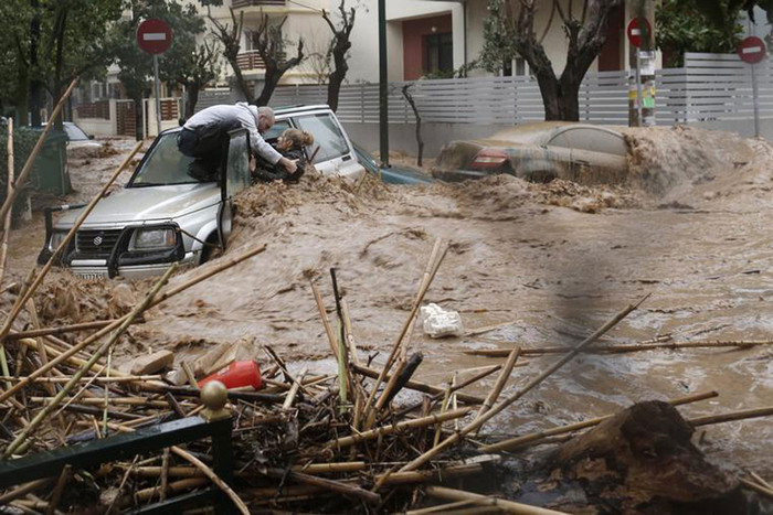 A woman is rescued from flood waters by a resident standing on top of her car during heavy rain in Chalandri suburb north of Athens (Reuters)