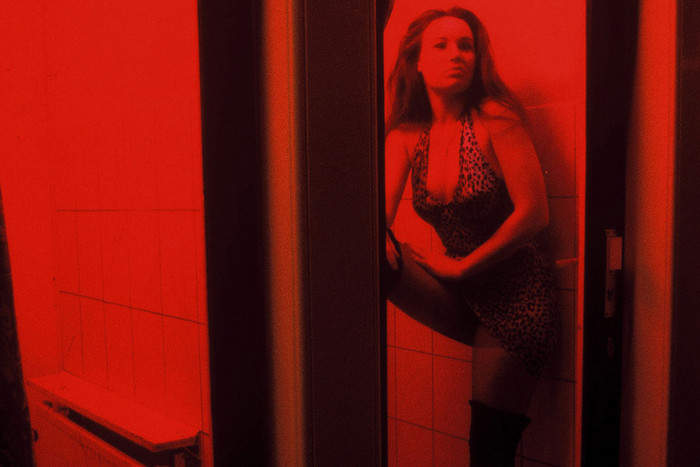 A Dutch prostitute sits behind her window in the red light district in Amsterdam (Reuters)