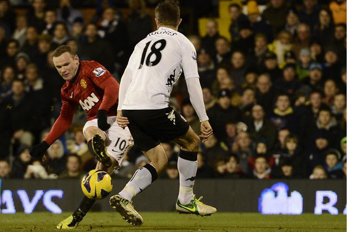 Wayne Rooney shoots the ball past Fulham's Hughes to score (Reuters)