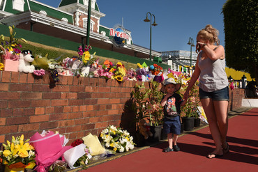 A mother and her child visit a floral tribute outside amusement theme park Dreamworld (AAP)