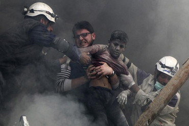 Men rescue a boy from under the rubble after bombing in Aleppo (Reuters)