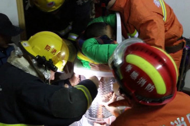 Two of the firefighters calmed the shaken boy down while holding him steady with their hands (APTN)