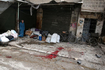 A woman stands near the blood-stained ground after strikes in Aleppo (Reuters)