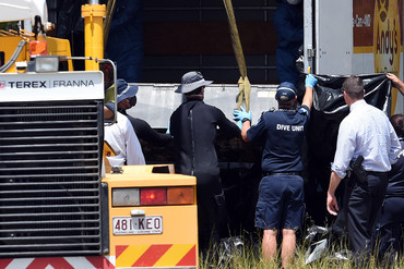 Police use a crane to load a metal box onto a truck at the scene where the bodies were reportedly found (AAP)