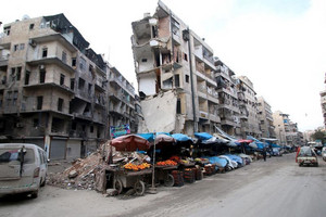 Stalls are seen on a street beside damaged buildings in Aleppo, Syria (Reuters)