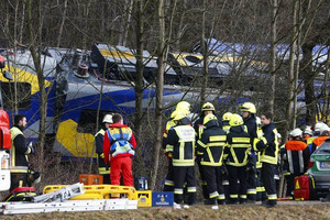 Members of emergency services stand next to the crashed train (Reuters)