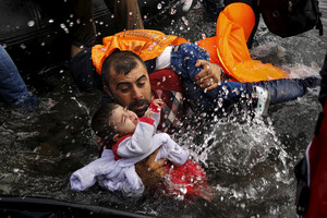 A Syrian refugee holds onto his children after crossing the Aegean Sea from Turkey to Lesbos. (Reuters)