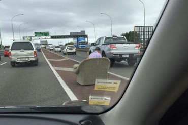 A man waits on an armchair in the middle of Auckland Harbour Bridge (Photo: imgur.com)