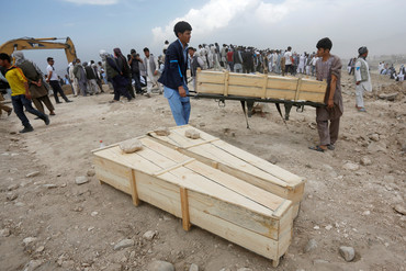 Afghan men carry empty coffins for the victims of yesterday's suicide attack in Kabul (Reuters)