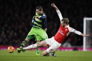 Per Mertesacker attempts to tackle Gylfi Sigurdsson (Reuters)