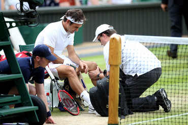 Roger Federer receives treatment on his knee during Wimbledon (AAP)