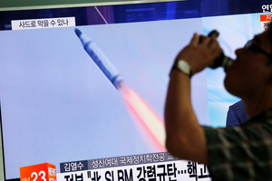 A man in Seoul walks past a TV screen broadcasting a news report on North Korea's submarine-launched ballistic missile (Reuters)