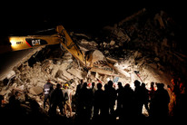 Rescuers work in the night at a collapsed house in Pescara del Tronto (Reuters)