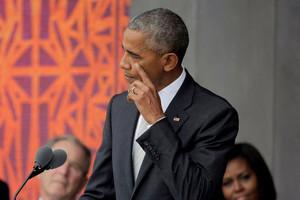President Obama wipes his cheek as he speaks (Reuters)