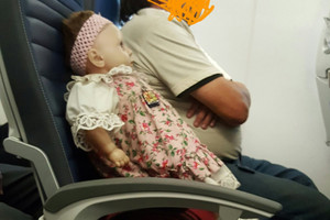 The doll, named Barbara, strapped in on her Red Eye flight (Twitter / Sara Novic)