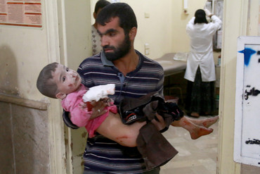 A Syrian man carries his son to a field hospital after Syrian and Russian army carried out an airstrike (Getty(